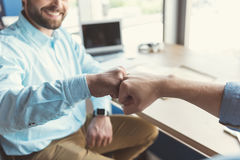 Happy youthful guy communicating with coworker in office Royalty Free Stock Photography