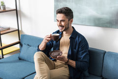 Happy youthful guy having leisure time in his apartment Royalty Free Stock Images