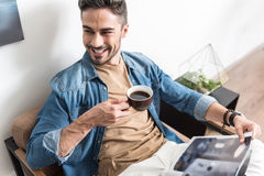 Happy youthful guy spending free time with hot beverage indoors Royalty Free Stock Photography