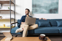 Happy youthful guy working at home via computer Royalty Free Stock Image