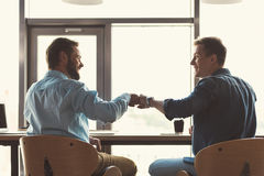 Happy youthful guys cooperating together at work in office Stock Image