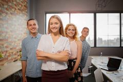 Portrait of smiling woman in office, colleagues on the background. stock images