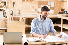 Happy youthful lumber craftsman creating sketches at his workplace Royalty Free Stock Image