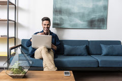Happy youthful man having rest using notebook at home Royalty Free Stock Images