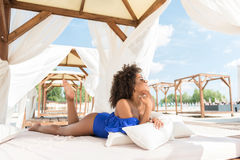 Happy youthful mulatto girl taking pleasure of summer resort. Cheerful young agrican woman is lying on large wooden sun bed with roof and drapes. She is leaning Royalty Free Stock Photos
