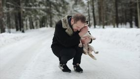 Happyattractive young man in black coathaving with a her beagle dog in a winter day. Friendship, pet and human. Candid. And authentic footage. Slow motion stock video