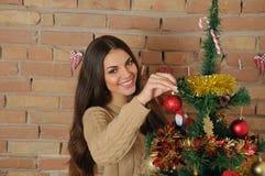 Happyl ung kvinna som hemma dekorerar julgranen för ferie Arkivfoto