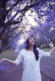 Happyl woman in white dress standing in street surrounded by purple falling Jacaranda blooms Stock Photos
