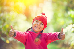 Happyness. Happy little girl showing thumbs up in sunny day Stock Image