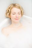Happyness. Happy young woman relaxing in the bath Stock Image