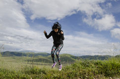 Happyness. Young woman jumping over the meadow Stock Images