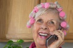HappySenior Frau in den rosafarbenen Lockenwicklern auf ihrem Zellen-Phon Stockfotos