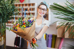 Happywoman florist giving bouquet of colorful flowers to you Stock Images