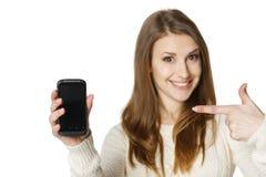 Happywoman que señala en su teléfono móvil Foto de archivo