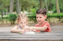 Hapy dzieciaki uczą się w parku Brat i siostra wpólnie robimy j zdjęcie stock