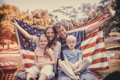Hapy family holding american flag in the park Stock Photo
