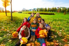 Hapy kids in the park. Group of happy kids sit in the park on the grass holding bouquets of autumn maple leaves and smiling stock photo