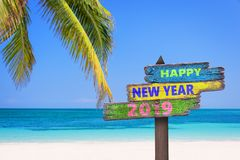 Hapy new year 2019 on a colored wood direction signs, beach and palm tree background stock photography