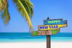 Hapy new year 2018 on a colored wooden direction signs, beach and palm tree. Background stock image