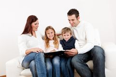 Hapy young family watching photo album. At home Royalty Free Stock Image