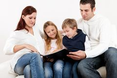 Hapy young family watching photo album. At home Royalty Free Stock Photos