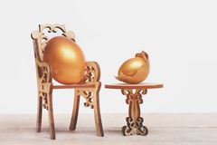 Easter golden egg on wooden chair at table, future life. Hapyy easter holidays eggs and bunny eating and cooking, healthy food, golden eggs in broken shell Royalty Free Stock Photography