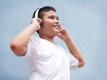 Asian boy wearing headphone over blue wall background. Stock Image