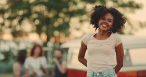Har den afrikanska flickan för closeupen med lockigt hår som hoppar framme av kameran på picknicken, ett härligt leende och som ä lager videofilmer