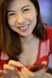Har den asiatiska kvinnan för leendet gyckel med mobiltelefonen Arkivbilder
