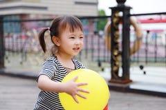 Har den färgrika ballongen för lycklig liten gullig älskvärd för barnleendet för flickan kinesisk lek för skrattet gyckel på somm royaltyfria foton