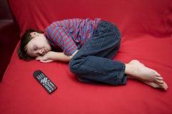 har den sovande pojken fallna framdelen tv:n som Fotografering för Bildbyråer