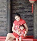 har den unga kinesiska modern för den lyckliga familjen gyckel med att behandla som ett barn i Kina traditionell cheongsam Royaltyfri Foto
