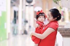 har den unga kinesiska modern för den lyckliga familjen gyckel med att behandla som ett barn i Kina traditionell cheongsam Fotografering för Bildbyråer