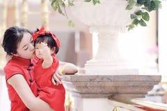 har den unga kinesiska modern för den lyckliga familjen gyckel med att behandla som ett barn i Kina traditionell cheongsam Arkivbilder