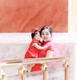 har den unga kinesiska modern för den lyckliga familjen gyckel med att behandla som ett barn i Kina traditionell cheongsam Royaltyfri Bild
