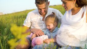 Har gravida par för Closeup med litet barndottern fritid utomhus i gräsfält på filten lager videofilmer