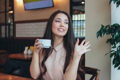 Har långt hår för den härliga charmiga brunetten som ler den asiatiska flickan, frukosten med kaffe på kafét och att vinka till v royaltyfri foto