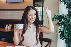 Har långt hår för den härliga charmiga brunetten som ler den asiatiska flickan, frukosten med kaffe på kafét och att vinka till v fotografering för bildbyråer