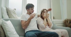 Har sjuka par för modern vardagsrum på soffan en rinnande näsa och en dålig bärande a pyjamas för känsla lager videofilmer