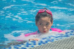 Har tycker om den asiatiska gulliga lilla flickan f?r lycka rolig k?nsla och i simbass?ng royaltyfri bild