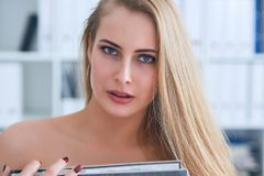 Beautiful young secretary hides her nakedness for a folder on an office background. Harassment concept. stock photo