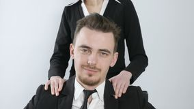 Harassment. Female hands are massaging the shoulders of a young businessman in a suit. Successful boss happy, smiling 60. Female hands are massaging the stock video