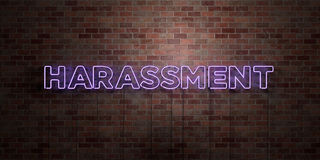 HARASSMENT - fluorescent Neon tube Sign on brickwork - Front view - 3D rendered royalty free stock picture Royalty Free Stock Photos