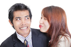 Harassment at the job. Young Asian businesswoman or office worker trying to approach and to kiss her male colleague that  apparent by his reluctant and Royalty Free Stock Photography