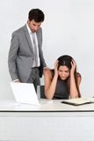 Harassment at work. Businessman in office harassing young woman Stock Images