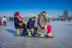 Harbin, China - February 9, 2017: Friends on a sled having fun on frozen river Songhua during winter time. Stock Images