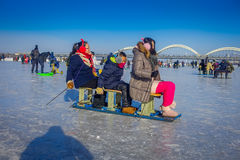 Harbin, China - February 9, 2017: Friends on a sled having fun on frozen river Songhua during winter time. Stock Photo
