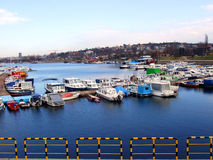 Harbor. Boats docked in blue water in harbor with populated hillside in background, railing in foreground royalty free stock photos