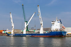 Harbor of Antwerp with cargo ships moored at quay with big cranes Royalty Free Stock Photo