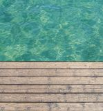 Harbor board and deck path made of wood with turquoise sea. Background Royalty Free Stock Image